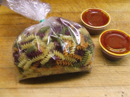 Save the small container of sauce that come with your pizza order.  Use any Pasta on hand.  I like the multi-flavor Pasta.