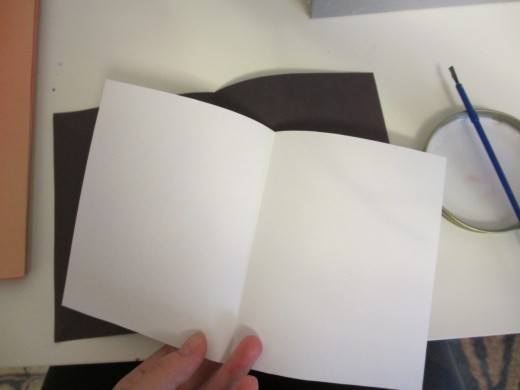 Cut the white paper slightly smaller than the construction paper on all sides.