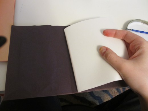 Press the glued fold into the crease in the construction paper.