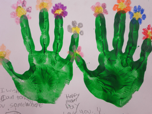 This hand-print art was done with tempera paint then the child used oil pastels to draw the flowers on the top of their hand-print.