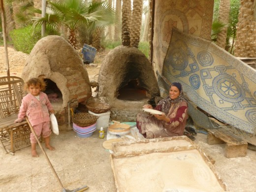 Lady who fixed us Egyptian bread in an earthen oven and her child. Copyright REKongaika