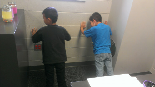 Two boys doing wall push-ups.