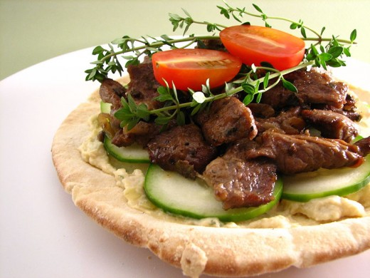 Pita topped with hummus lamb and salad.