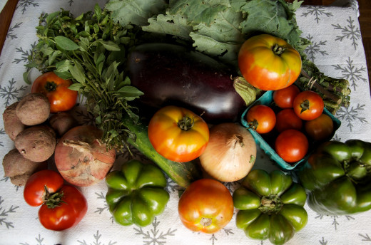Produce seen here in no particular order:  slicing tomatoes, cherry tomatoes, mixed peppers, red potatoes, eggplant, walla walla onion, Russian kale, cucumber, and lemon basil.