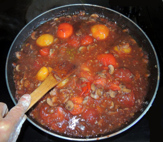 using a wooden spoon/spatula, break apart tomatoes and mix into sauce. Tomatoes should break easily at this juncture.