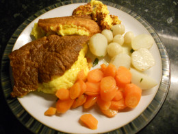 Cheese souffle served with minted baby new potatoes and buttered carrots