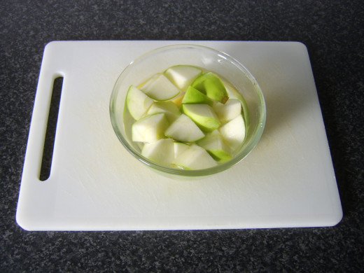 Apple pieces are added to water and lemon juice