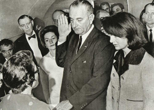 President Johnson being sworn in on Air Force One with Mrs. Kennedy still wearing suit smeared with President Kennedy's blood