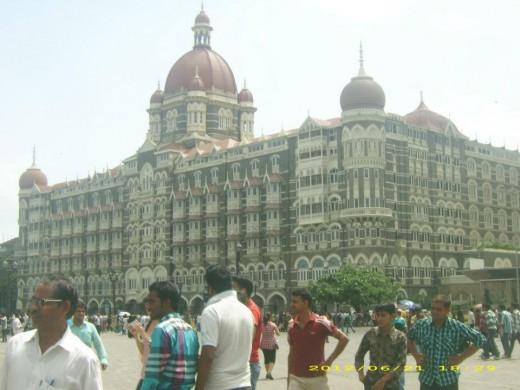 "Tourists enjoy the engineering marvel called ""Taj Hotel"""