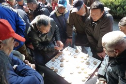 4 d) Senior Chinese men playing a board game at Temple of Heaven grounds