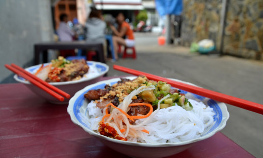 Rice vermicelli salad with fresh vegetables, ground red chillies, sweet barbecued pork, ground peanuts, and chopped pickled vegetables.