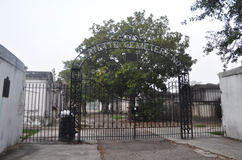 The gates of Lafayette No. 1, with a hanging plaque dedicating the cemetery to Theodore Von LaHache, the founder of the New Orleans Philharmonic Society