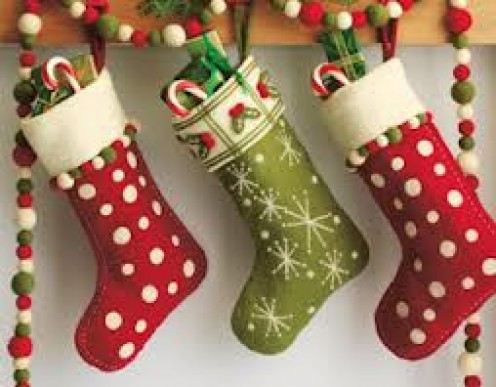Christmas Stockings hang on the fireplace and parents fill them with candy, fruit and gifts for their children.