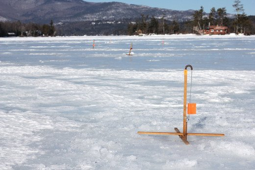 Several ice fishing rods set up on the ice.