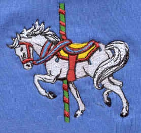 An embroidered carousel horse with bright colors in the saddle