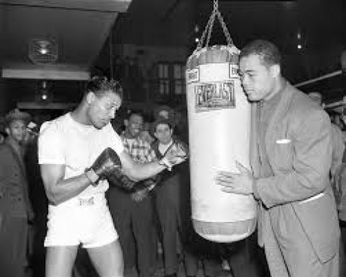 Sugar Ray Robinson throws a jab at a heavybag that Joe Louis is holding. Robinson is considered pound for pound the best boxer in history.