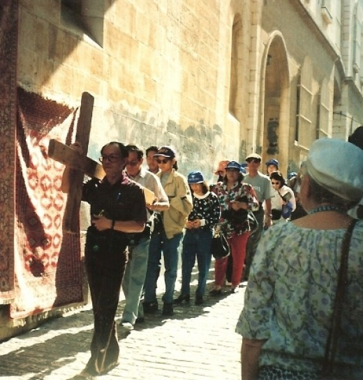 Tourists can rent a cross and carry it through Via Dolorosa street