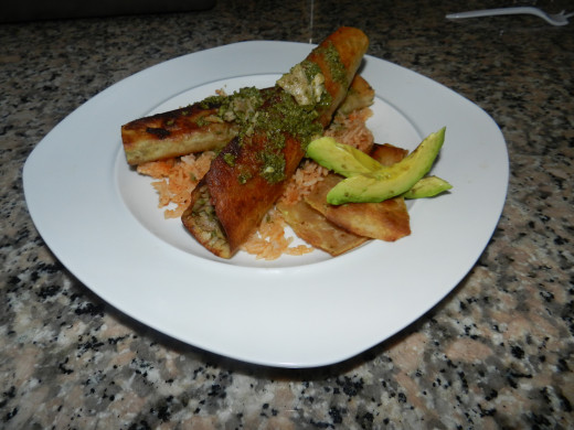 (Pork) Flautas Verde over a bed of Spanish rice with a side of fresh tortilla chips and avocado.