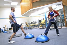 Personal trainer showing a client how to exercise the right way and educating them along the way. The semi-spherical device is a BOSU.