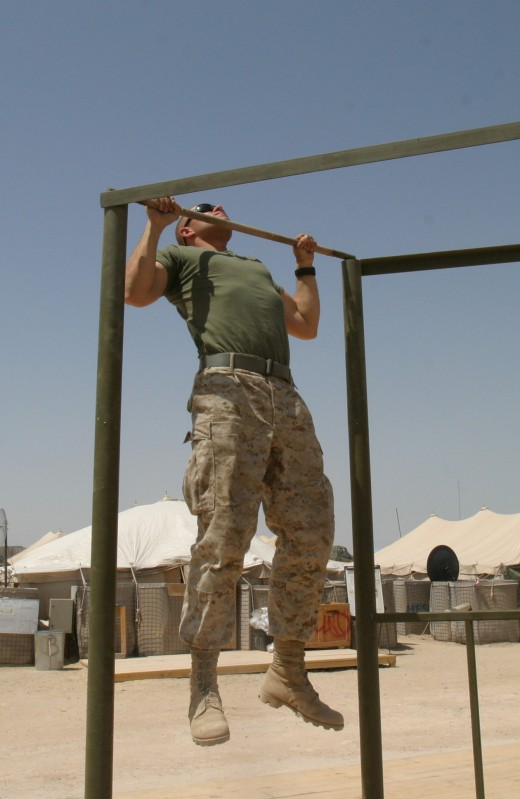A Marine at the apex position of a pullup.