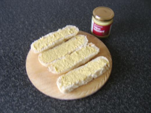 Dijon mustard is spread on halved subs
