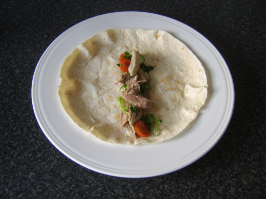 Watercress salad and turkey is arranged on tortilla wrap