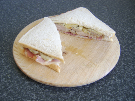 Turkey, bacon and melted cheese sandwich is sliced for service