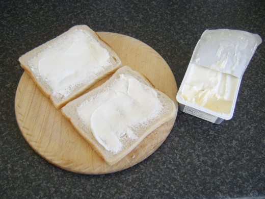 Cream cheese is spread on two slices of bread