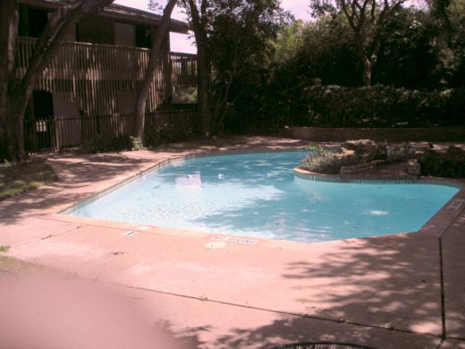 This photo of the swimming pool shows the back doors to the apartments in the complex.