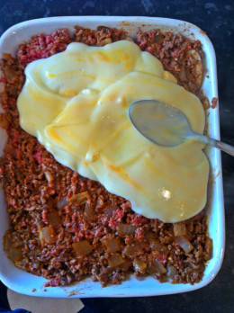 Spread over with mince and cheese sauce