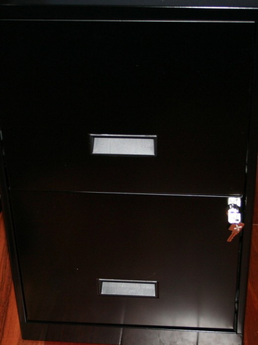 Inexpensive two-drawer file cabinet.  Top drawer contains files.  Bottom drawer contains envelopes and mailing supplies.  I keep my postage meter on top of the cabinet by my desk for quick access to weighing parcels.