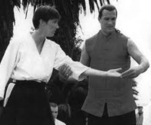 Steven Seagal teaching Aikido to a student. He has been practicing and teaching martial arts for many years and he is an expert in the field.