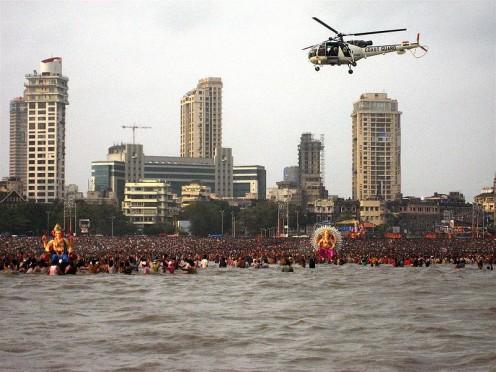 Un costo Indian Guaard helicóptero patrullas un ritual Ganesh Visarjan en Chowpatty Beach, Mumabi