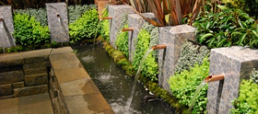 Retaining wall with water elements, (up close view) copper spouts and greenery.