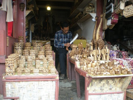 A man works on a craft and sell the product at his shop.