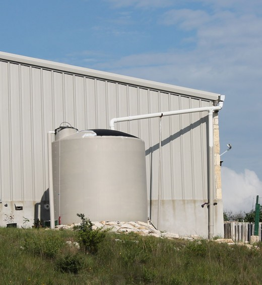 This large rainwater plastic collection tank is supplying a barn style home.