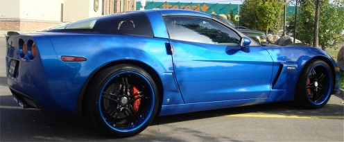 A Chevrolet Corvette equipped with distinctive black wheels that feature a color-matched pinstripe on the lip