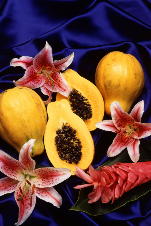 tropical papaya fruit displayed with tropical flowers.