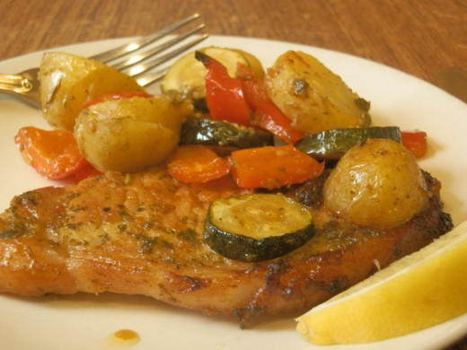 pork chop and roasted vegetables on plate, with slice of lemon to garnish