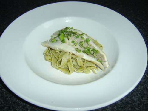 Grilled coley fillet is laid on a bed of linguine pasta with green pesto sauce