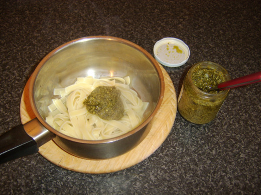 Green pesto sauce is added to drained linguine