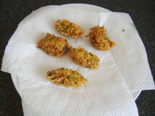 Deep fried sweet potato fritters are drained on kitchen paper