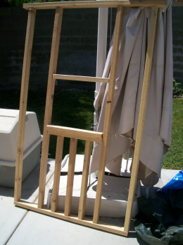 The framed back wall leaning against a patio umbrella that is about to cast its last shade.
