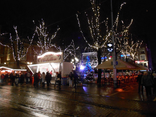 The Leidseplein area at night, lit up with holiday lights in December. The small lit up booth sells pastries on the street.