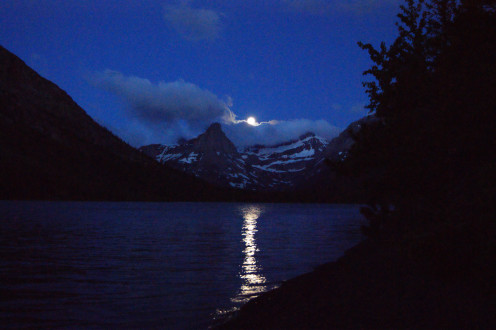 The moon sets over mountain peaks in Glacier National Park on a recent backpacking trip to Cosley Lake.