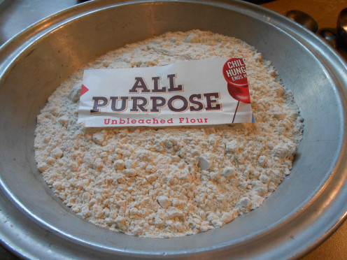 Use a pie plate for dredging chicken leg quarters in flour and spices before baking.
