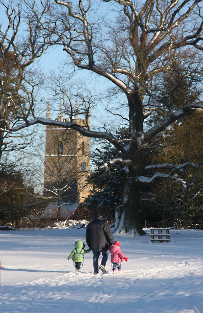 Fun day out with Granddad; two happy children and their grandfather run through thick snow just inside the entrance to Ickworth Park, at Horringer near Suffolk, Great Britain. Behind is the parish church of the village, St Leonard's, 12/20/2009.