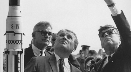 """1961, actually a huge giant, JFK is on board with going to the moon and looking cool wearing shades. Here he plays the cool guy showing other giants which way the tiny human rocket will go to the moon. """"Basically, up there, guys, real high up."""""""