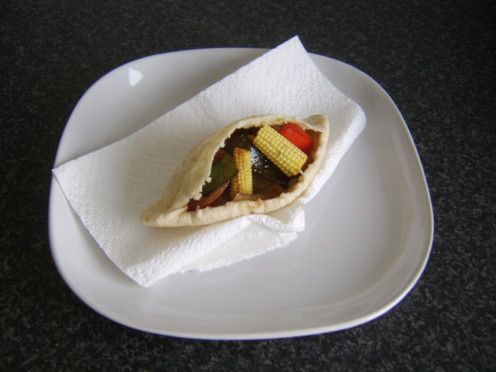 Assorted vegetables stir fried with soy sauce and incorporated in a pitta bread sandwich