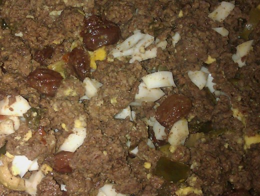 This is what the cooked filling looks like at the end of it all. The ground beef will have absorbed not only the flavor of the ground spices (cumin and hot red pepper), but also of the raisins, green bell pepper, green olives and hard boiled eggs.